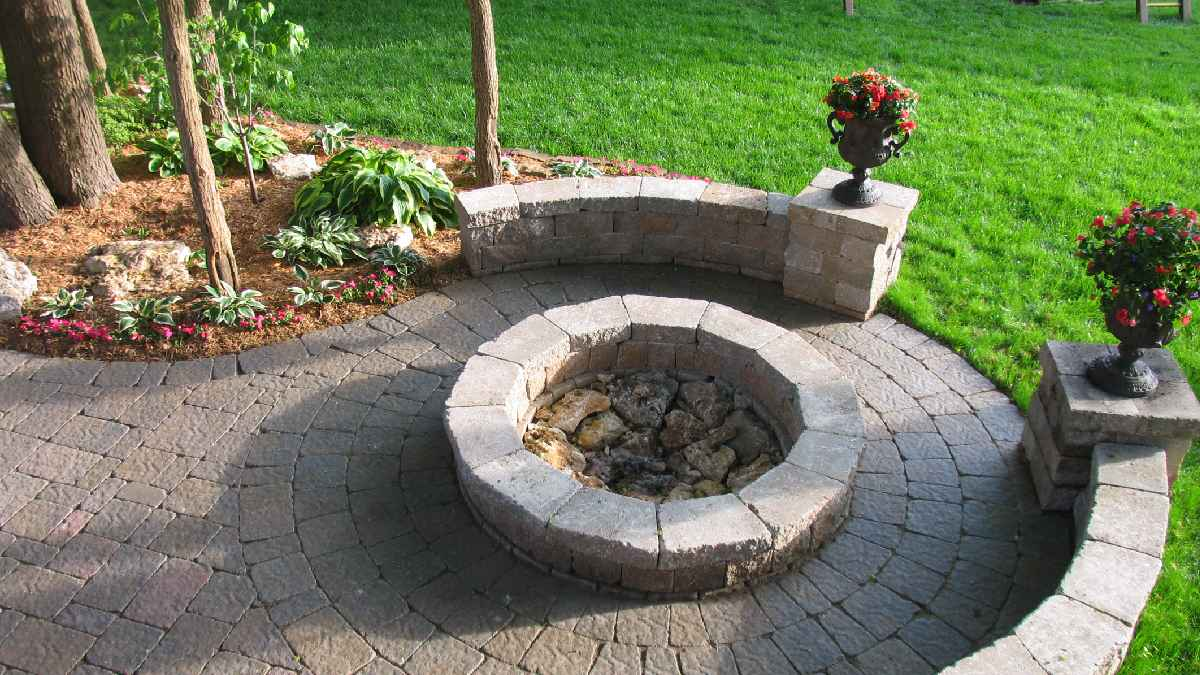 Brick fire pit on circular patio with landscaping surrounding